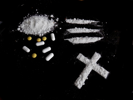 Cocaine drug powder, lines and cross and pills on black background Standard-Bild