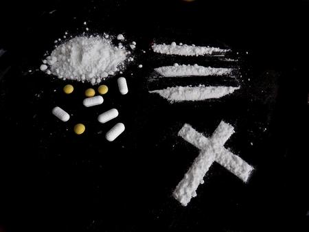 Cocaine drug powder, lines and cross and pills on black background Lizenzfreie Bilder