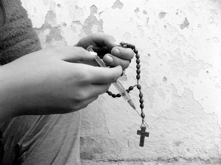 Young women holding rosary and drug injection in palms, young girl using drugs