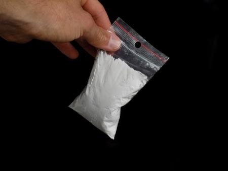 Drug dealer holding bag with cocaine drug powder, men selling drugs junkie