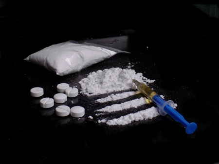 Injection syringe on cocaine drug powder and pile, cocaine bag and pills on black background