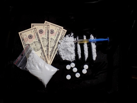 Injection syringe on cocaine drug powder pile and lines, pills, cocaine bag, dollar money bills on black background Standard-Bild