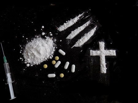 Cocaine drug powder pile, lines and cross, pills and injection syringe on black background Standard-Bild