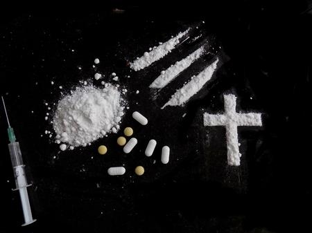Cocaine drug powder pile, lines and cross, pills and injection syringe on black background Lizenzfreie Bilder