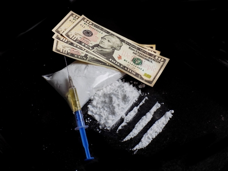 Injection syringe on cocaine drug powder bag, pile and lines and dollar money bills on black background Standard-Bild