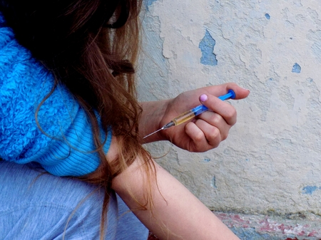Young woman using drugs in injection, young girl with drug injection in palm, drug addiction Standard-Bild