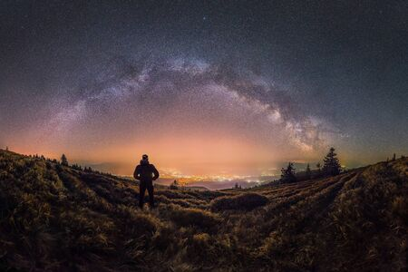 Person looks at the city and Milky Way glowing in the sky