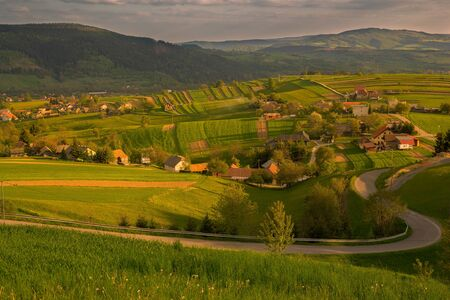The sunset light casts shadows on the countryside and fields of local peasants