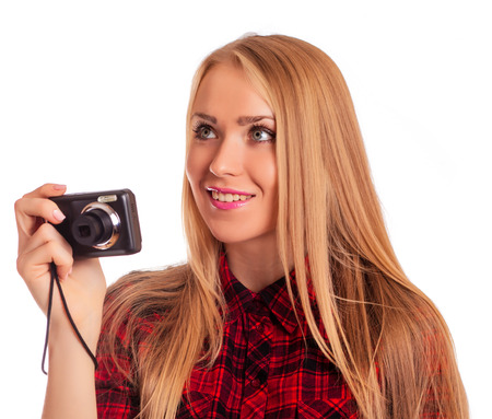 compact camera: Glamour woman photographer holding a compact camera and shooting - isolated on white