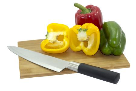 cuchillo de cocina: Aislado de tres pimientos sobre tabla de cortar de madera con un cuchillo de cocina