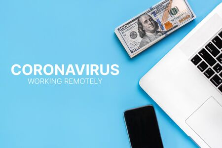 The concept of working from home during a coronavirus epidemic. People work remotely. Laptop and banknotes on a blue background. Covid-19