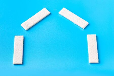 Chewing gum on a blue background that can be used for lettering. Chewing gum is laid out in the shape of a house
