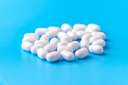 White dragees lie in a pile on a blue background. Close-up, macro photography. Lots of white mints