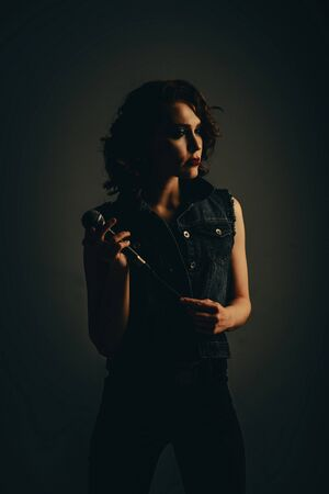 A girl with a microphone in her hands on a dark background. Art photo of a girl, a singer with a microphone. Stock Photo