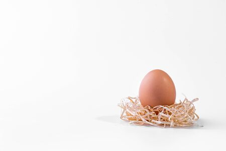 Fresh chicken egg in a nest of straw isolated on a white background