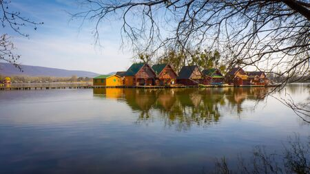 Tata, Hungary - Small wooden fisherman houses at Lake Derito on an island with reflection. The image is surrounded by tree branches.