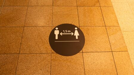 A social distance warning sign on the ground in a shopping mall.The mark was placed because of the coronavirus.