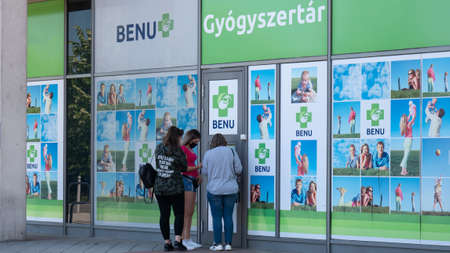 Gyor Hungary 05 22 2020: Young girls buy a medical protective mask against coronavirus in a benu pharmacy. The mask is released through a small window to avoid social contact.