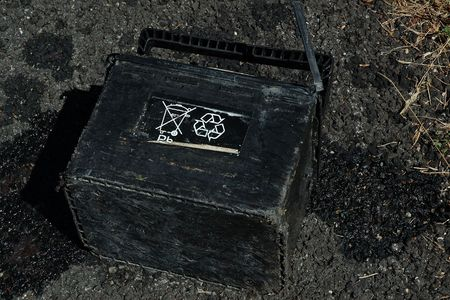 A leaking car battery left on the road and showing the Do Not Throw in the Garbages and Recyclable symbols face up . Horizontal close up. Imagens