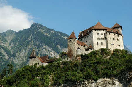 liechtenstein: The manificent Gutenberg Castle in Balzers, Liechtenstein. Blue Sky and mountains in the background. This castle, the emblem of Balzers is 70 meters high over the village and was built in the 13th century Stock Photo