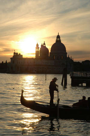 venice: Whilst the sun falls behind the Church of Madonna Della Salute in Dorsoduro , Venice , a gondolier passes left to right on the foreground.