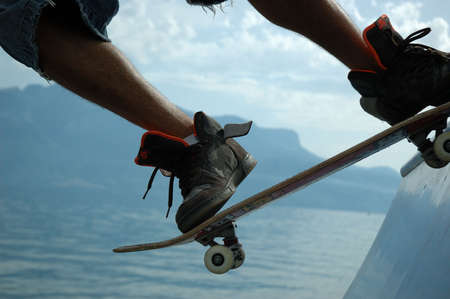 Close-up shot of a skateboarder on a ramp with Lake Leman and the Alps in the background