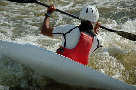 Close shot from behind of a kayaker fighting the rapids.