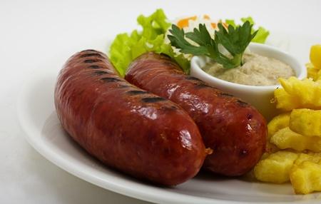 chorizos asados: Salchichas a la parrilla con patatas y salsa