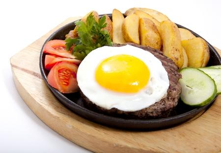 huevos fritos: Foto del filete con patatas y huevo en una sartén
