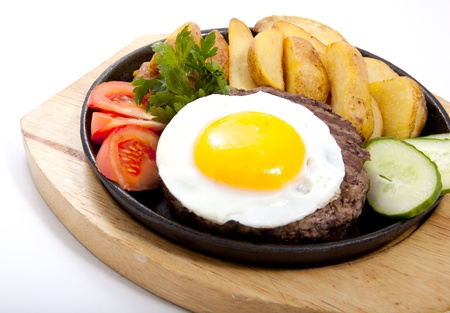 plateful: Photo of steak with potatoes and egg in a frying pan
