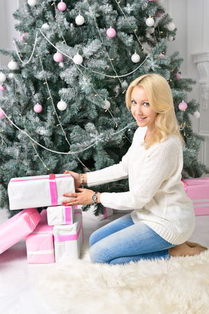 colorfully: A blonde woman unwraping colorfully packed New Year presents