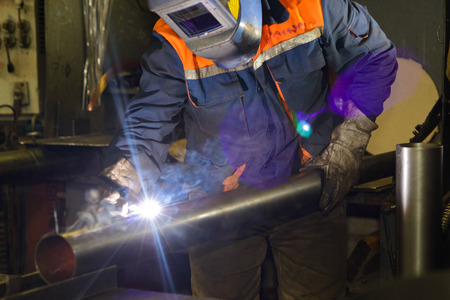 characteristic: A welder profession. A worker is welding a metal framework juncture