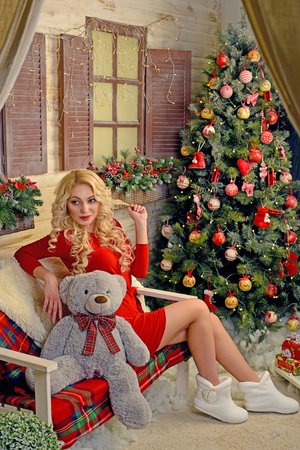 A girl sits on a bench in the room next to a Christmas tree. Next to her teddy bear. Volgograd region, Russia, November 8, 2015