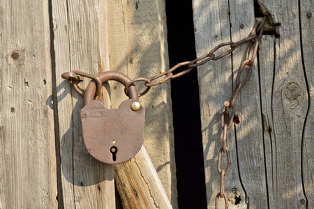 An old padlock, attached to the wooden door with a rusty chain