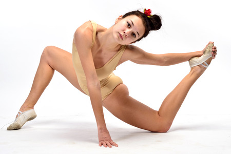 A girl in a brown bodysuit is doing stretching excercises (isolation on white)