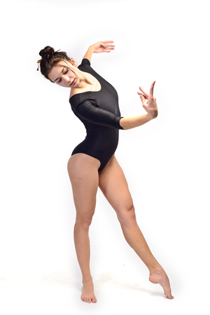 A woman gymnast in a black sporty swimming suit  is doing stretching exercises (isolated on white) 스톡 콘텐츠