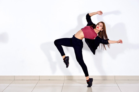 Young dancer, girl dancing, dance moves choreographed the work on themselves, against a white wall. Frozen jump on white background. Banque d'images