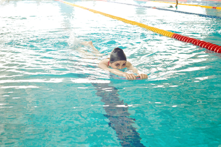 A young girl swims in the pool with a supporting Board for practicing smooth movement on the surface of the track.