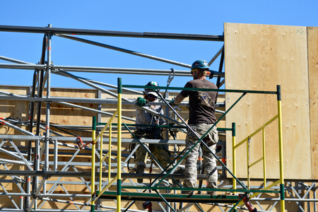 Pair of mounting work fixed plywood panels on top, working on specially constructed scaffolding.  Volgograd, Russia 27 may 2018