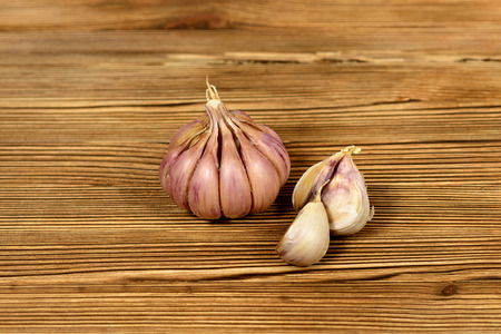 Onion and a pair of garlic cloves, lie on a dark, textured, wooden background, close-up Imagens