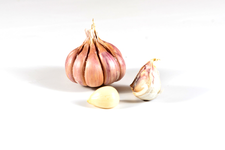 Onion and a pair of garlic cloves, lie on a white background, close-up