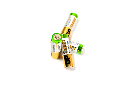 Several spent color alkaline batteries on a white background. Russia, Volgograd, August 19, 2018