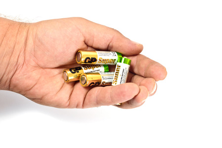 Several spent color alkaline batteries in the hand of a man on a white background. Recycling, energy, energy, environment and ecology concept-close your hands holding alkaline batteries pile. Russia, Volgograd, August 19, 2018