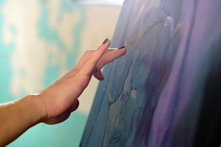 The womans hand is directed to the prepared canvas to grind the remains of the primer before starting to draw