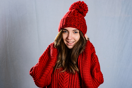 Fashionable young woman posing ,wearing red knitted sweater and red cap. Elegant woman wearing trendy outfit.Fashion portrait of beautiful young woman. Imagens