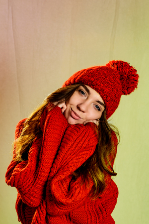 The nice girl in a red knitted sweater and a knitted hat with a pompom, holds her hands on her cheeks and smiles tenderly