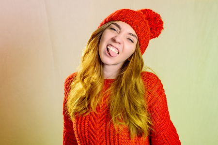 The beautiful young girl wearing red hat and sweater. She is having fun, showing her pink tongue