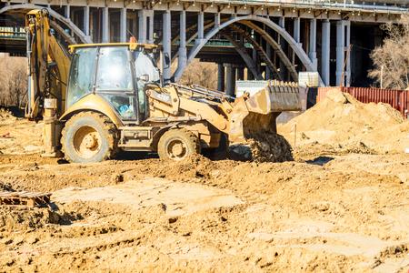 Excavadora cargadora de ruedas descargando arena durante los trabajos de movimiento de tierra en el sitio de construcción. Foto de archivo
