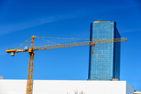 Yellow crane and blue sky on building site, against the background glass shard building