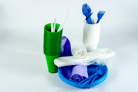 The bright plastic tableware and rolls with polythene packaging on light grey background Imagens